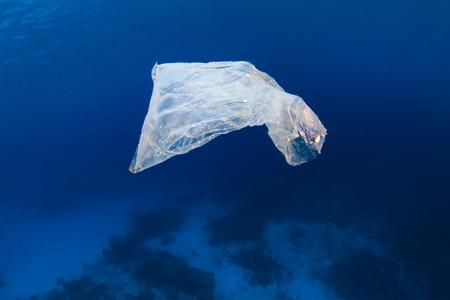 해양 오염 - 폐기 된 플라스틱 패킷이 그렇지 않으면 건강한 열대 산호초 위의 바다에 떠 있습니다.