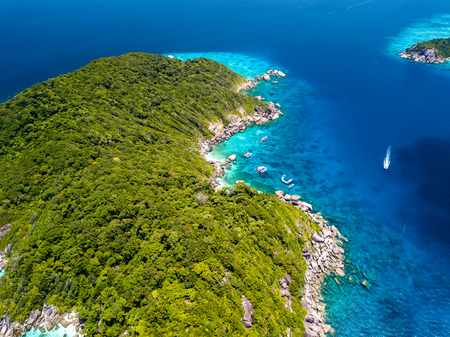 Aerial drone view of a boat over a coral reef next to a beautiful, empty, tree covered island Banque d'images
