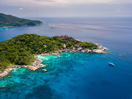 Drone view of a boat in a clear ocean next to tree covered tropical islands (Similan Islands, Thailand)