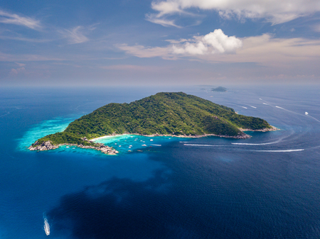 Aerial drone view of boats around the tree covered island of Ko Similan in Thailand