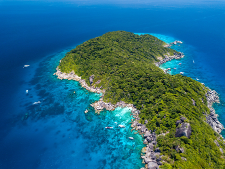 Aerial view of a boat moored in crystal clear waters over a coral reef next to a deserted, tree covered tropical island