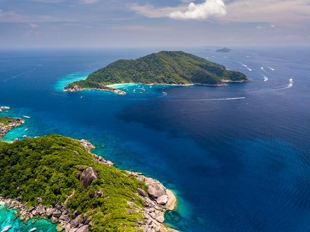 Aerial drone view of boats around the clear waters and tree covered Similan Islands in Thailand Stock Photo
