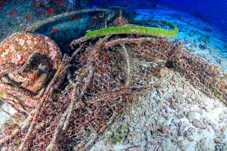 Abandoned fishing equipment polluting a tropical coral reef Stock Photo