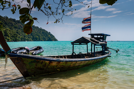 Traditional wooden Longtail boat on a tropical sandy beach surrounded by jungle