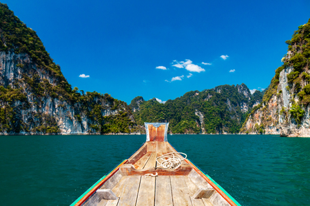 Traditional boat on a beautiful lake surrounded by towering cliffs and jungle
