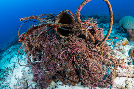 An abandoned fishing net polluting a tropical coral reef Stock Photo