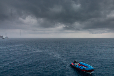 Small boat in a rough ocean and tropical thunderstorm
