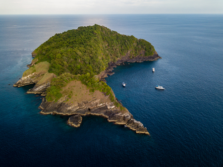 Aerial drone view of tropical Koh Bon island with several dive boats in the bay