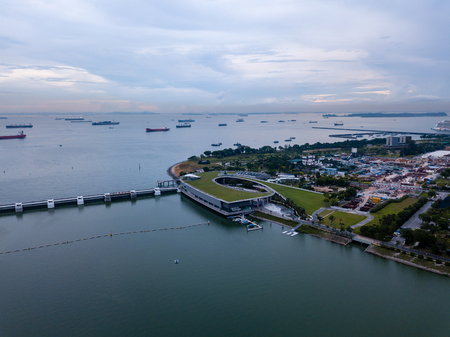 Aerial drone view of Singapore Marina Barrage with ships waiting out to sea