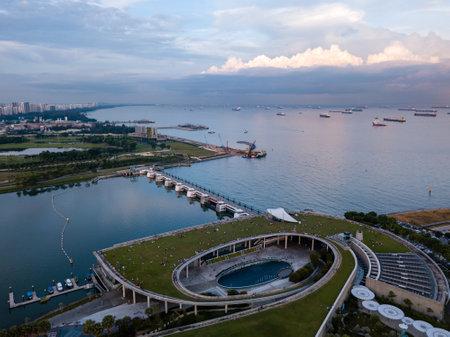 Luftdrohnenansicht von Singapore Marina Barrage mit Schiffen, die auf See warten