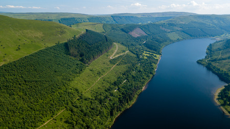 Aerial view of a large reservoir in a deep valley surrounded by green fields (Tal-y-Bont, Wales) Stock Photo