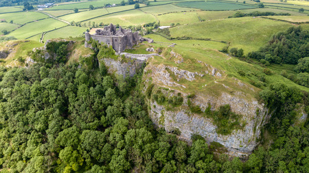 Aerial view of a ruined castle overlooking rural farmland in Wales (Britain)
