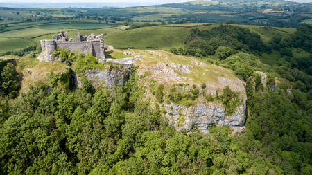 Aerial view of the ruins of an ancient castle on a hilltop (Carreg Cennen, Wales, Britain)
