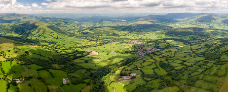 Panoramic aerial view of green farmland and fields in the rural Welsh countryside