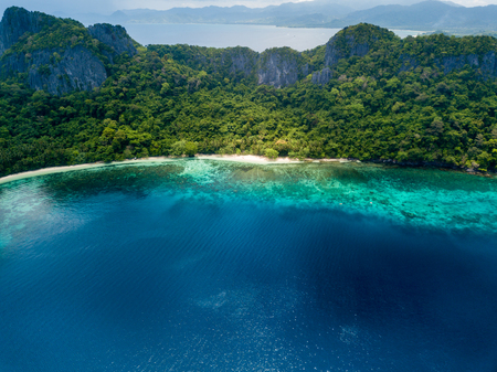 Aerial drone view of a beautiful deserted tropical beach surrounded by large cliffs and jungle (Cadlao Island, El Nido, Palawan) Imagens