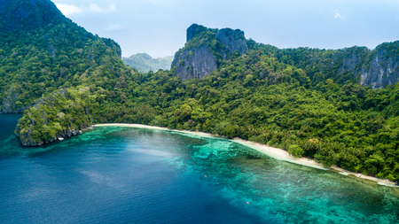 Drone view of a beautiful deserted tropical island with jungle, cliffs and fringed by coral reef
