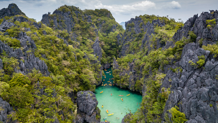 Aerial drone view of kayaks inside a beautiful shallow tropical lagoon surrounded by jagged cliffs and jungle (Small Lagoon, El Nido) 写真素材