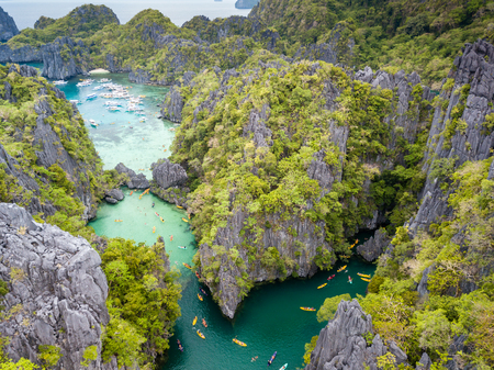 Aerial drone view of a beautiful tropical lagoon filled with kayaks and surrounded by jagged limestone cliffs (Small Lagoon, Miniloc Island, El Nido)