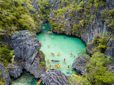 Aerial drone view of kayaks inside a beautiful shallow tropical lagoon surrounded by jagged cliffs and jungle (Small Lagoon, El Nido) Stock Photo