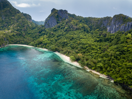Aerial drone view of a beautiful deserted tropical beach surrounded by large cliffs and jungle (Cadlao Island, El Nido, Palawan) 写真素材