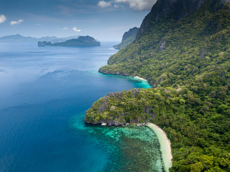 Aerial drone view of the tropical beaches and jungle of Cadlao Island, El Nido, Philippines