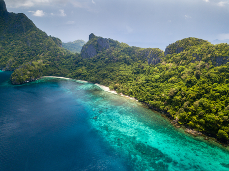 Aerial drone view of an unihabited tropical island with rugged mountains, jungle and sandy beaches