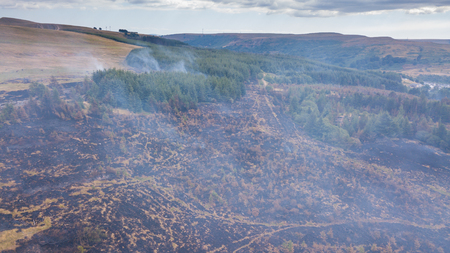 Aerial drone view of a smouldering wildfire in Wales, UK