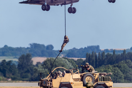 RNAS YEOVILTON, ENGLAND - July 07, 2018: A Royal Navy Merlin HC3 helicopter with troops on fastropes at the Yeovilton International Air Day as part of the Helicopter Force Role Demo at RNAS Yeovilton, England