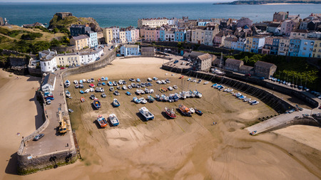 Aerial drone view of fishing boats beached at low tide in a harbour at the beautiful Welsh holiday resort of Tenby Stock Photo