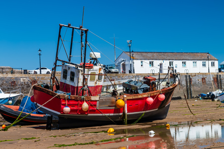 Colorful fishing and pleasure boats resting on the sand at a harbor during low tide on a sunny day Stock Photo