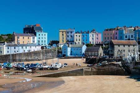 The colorful, picturesque Welsh town of Tenby with boats aground in the harbour at low tide