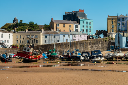 Picturesque harbor at low tide with boats resting on the sand waiting for the ocean to return