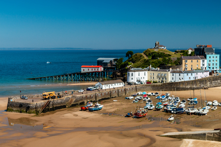 Colorful buildings and boats aground in harbour during low tide (Tenby, West Wales, UK)