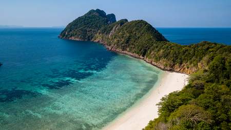 Aerial drone view of a small tropical island with lush green forest and a beautiful sandy beach with coral reef Archivio Fotografico