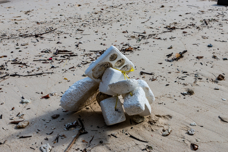 Polystyrene and other plastic rubbish washed up on a tropical beach on a remote island