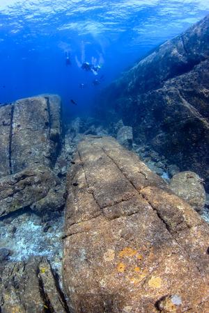 SCUBA divers exploring beautiful underwater scenery in a clear, tropical ocean