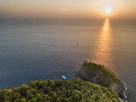 Aerial drone view of a tropical sunset next to a remote island with a single boat at anchor (Koh Bon)