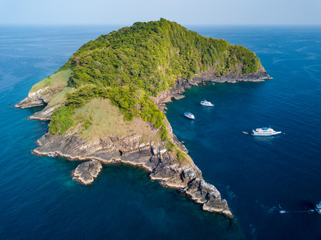 Aerial drone view of boats around a remote, jungle covered tropical island surrounded by fringing coral reef
