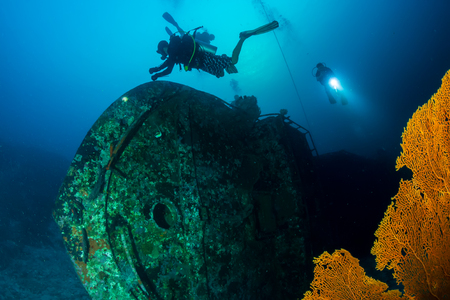 SCUBA divers exploring a large underwater shipwreck on a tropical coral reef