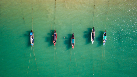 Aerial drone view of colorful traditional Longtail fishing boats at anchor in a shallow bay