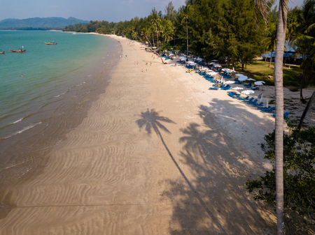 Aerial drone view of a long shadow of a palm tree cast onto a beautiful, empty tropical beach