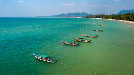 Aerial drone view of colorful traditional Longtail boats at anchor off a sandy beach in Thailand Stock Photo