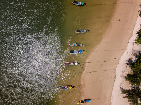 Aerial drone view of colorful, traditional Longtail boats moored off a sandy beach on the Andaman coast of Thailand