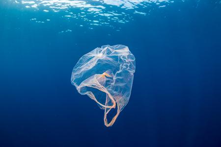 Unterwasserverschmutzung: - Eine weggeworfene Plastiktüte, die in einem tropischen Ozean mit blauem Wasser treibt