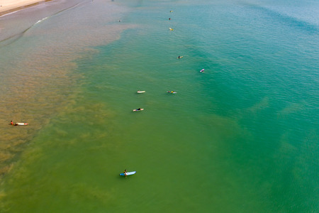 Aerial view of surfers waiting for waves in a shallow, tropical ocean Stock Photo