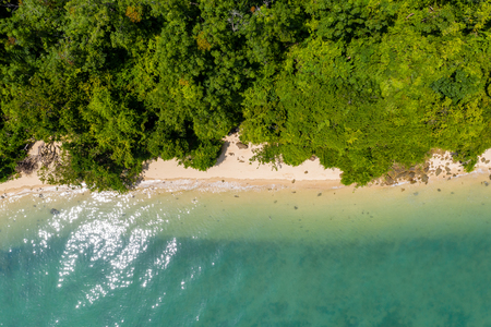 Aerial view of a beautiful tropical sandy beach surrounded by lush forest (Koh Yao Noi, Thailand)