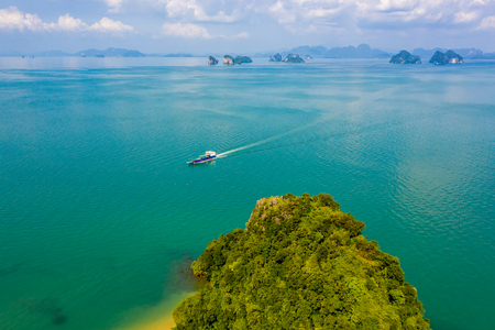 A ferry passing the tiny tropical island of Koh Nok in the Phanga Nga bay area of Thailand
