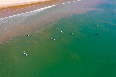 Aerial view of surfers in a shallow tropical ocean off a sandy beach