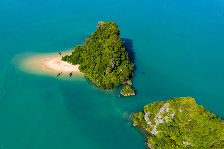 Aerial view of an exotic, tiny tropical island with sandy beach and jungle