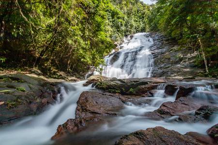 Long exposure of a picturesque waterfall flowing through a tropical rainforest Stok Fotoğraf